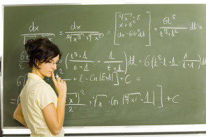 Teenage girl standing in classroom. Doing exercise on blackboard. Side view